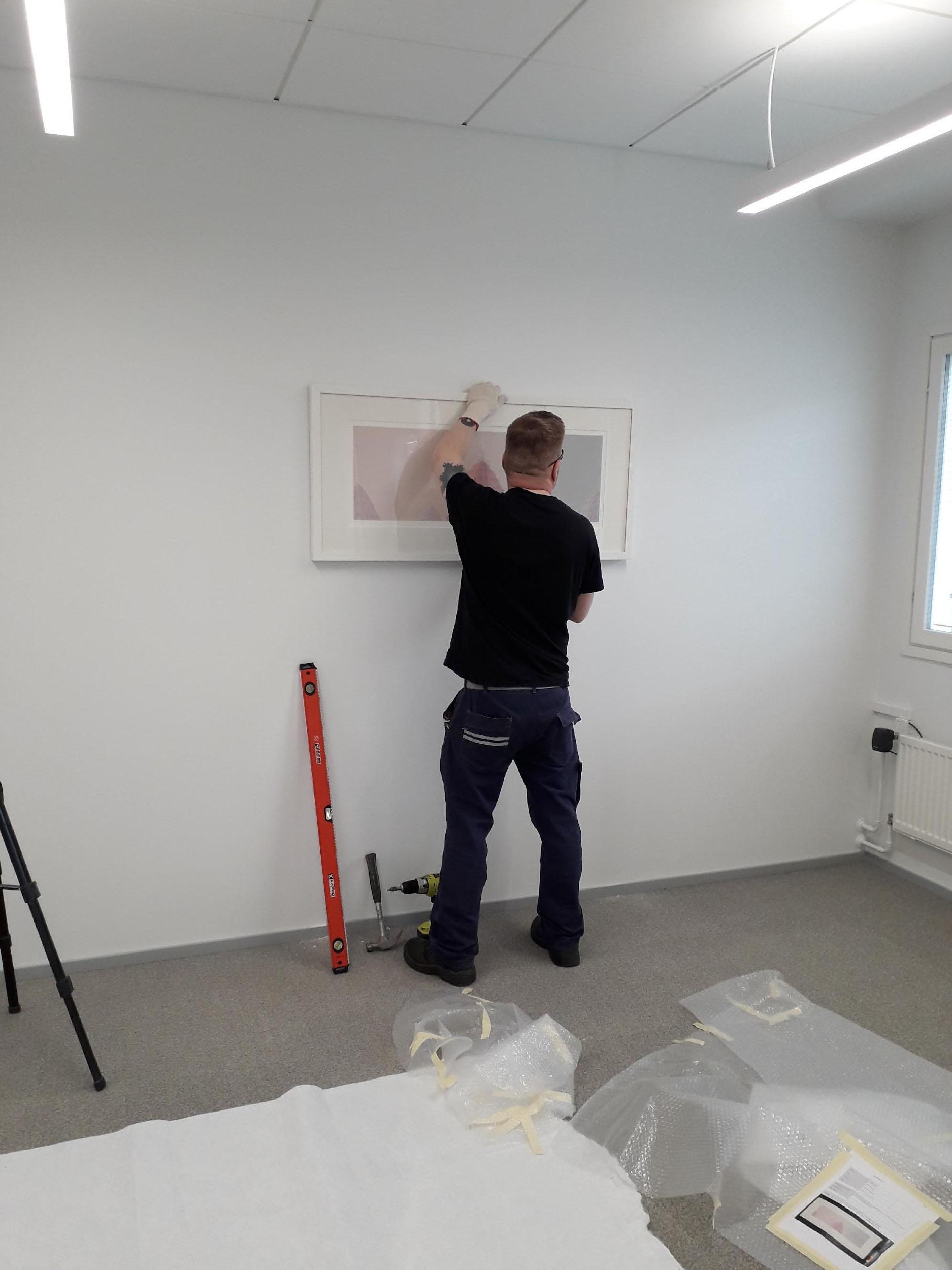 Jaani Föhr ripustaa Kristian Krokforsin teosta uusiin tiloihin. Kuva: Tiina Tolonen.
