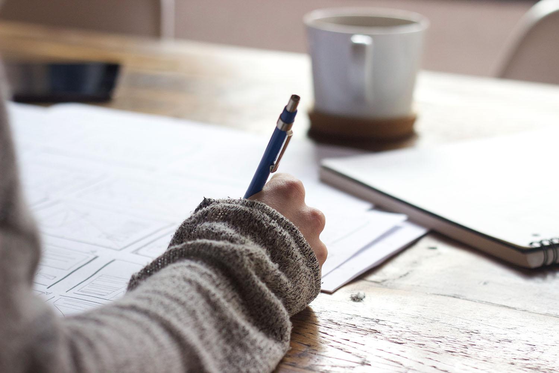 kuvassa käsi joka kirjoittaa, edessä kahvikuppi