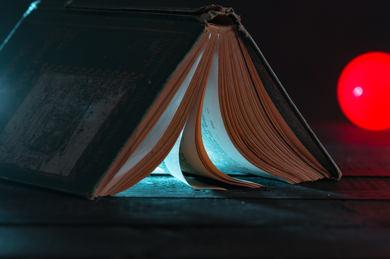 avattu kirja selkämys ylöspäin, takaa tulee valoa