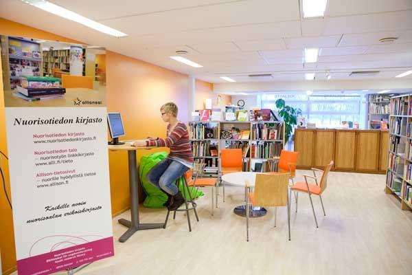 Nuorisotiedon kirjaston toinen informaatikko Anna Tiitinen tarkistaa kirjaston asiakaspäätteen toimivuutta