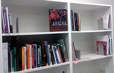 Perusluetteloituja kirjoja odottamassa sisällönkuvailua, eri tietokeskuksiin menevät omilla hyllyillään.