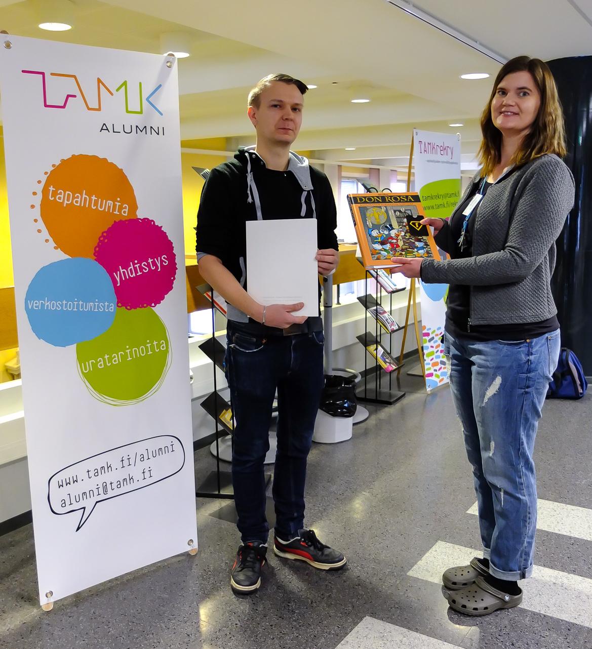 Kuva 1. Kirjaston suunnittelija Eija Mustonen onnittelee tietotekniikan koulutuksesta valmistunutta Aleksi Tapolaa.
